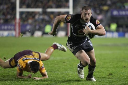 El jugador de rugby Lewis Brown superando a un rival con potencia.